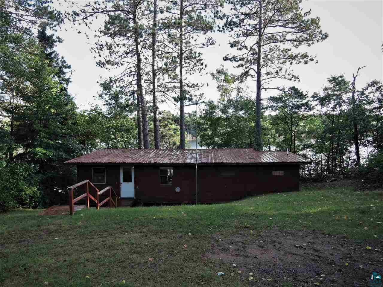 """There is deferred maintenance needed with this cabin, updated 220 amp service, new well pump,  and newer conventional septic system. Newer garage/workshop with 200 amp service. Seller will contribute $5,000 towards Buyer's closing costs or money towards any upgrades or repairs needed at closing with a successful sale. Make this your Northwoods hunting/fishing cabin now and a future home site located on 1.5 acres with 100' of sandy beach frontage with incredible southerly views on Pickerel Lake, also includes a newer 20' galvanized aluminum dock. Great location in Barnes with many other lakes and recreation trails and activities within minutes, an hour from Superior/Duluth, half-hour to Hayward, and Iron River. Fish for Northern, Walleye, Bass, and panfish, boating, canoeing, kayaking, paddleboat, and swimming in crystal clear water,  with sandy bottom and beach area. The rustic two-bedroom, one-bath cabin was remodeled in 1989 with a new deck and patio sliding door, metal roof, gas furnace unit in the kitchen, and 220-amp service. Newer garage in built-in 2003, with cement floor, 220-amp service, and garage door opener. The open area near the garage is a great location for a future home/cabin site Fire pit near sandy beach frontage and a picnic area with a picnic table included on level ground near the cabin.  Seller is motivated selling """"As Is""""  what you see is what you get in cabin and garage, including 16' fiberglass fishing boat with an Evinrude 70 HP motor, 12' V John boat, paddle boat, are included without warranty with a full asking price offer!"""