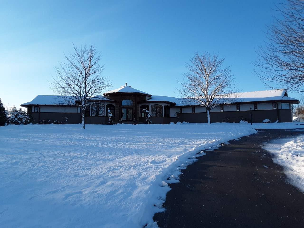 """Winter wonder land. Set back on almost 10 acres you will find this magnificent 6000 sqft walkout ranch. High ceilings, angled rooms, pillars, water feature & open concept give this beauty a unique flair. Large windows offer scenic views. 5 spacious BRs w/walk in closets, 4.5 baths & a expansive family room in LL perfect for entertaining. """"Other room"""" - mother in law suite. Enjoy hot tub in solarium or relax in outdoor living space that boasts stamped patio, pergola, professional landscaping & separate seating/fire area. 2 ponds,4 car garage w/circle driveway. $12,500 kitchen allowance"""