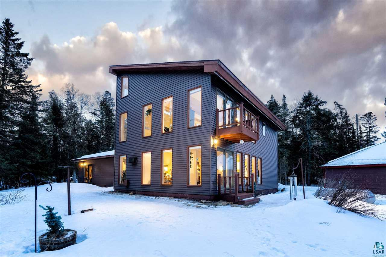 Peaceful, Serene location with breath taking views.  This 3 bedroom, 2.5 bath home sits on over 3 acres of land with a spectacular 877 ft of lake frontage with panoramic views.   The living room features 25 ft ceiling height with amazing views and a gas fireplace .  The upper level features a bedroom with million dollar views from every angle.  Not to mention the private deck.  Main floor master retreat with a private bath and walk out to the park like yard.  Formal dining room is open to the kitchen.  Enjoy doing dishes while watching the waves crash along the shoreline.  Another bedroom, office and main floor laundry complete the home.  Enjoy maintenance free steel siding.  40 year old roof was put on in 2014, septic put in 2006.  An additional 1.67 acres adjoining the property may be purchase separate with and additional lake frontage.  Just minutes to Superior and Duluth.  Don't let this one get away.