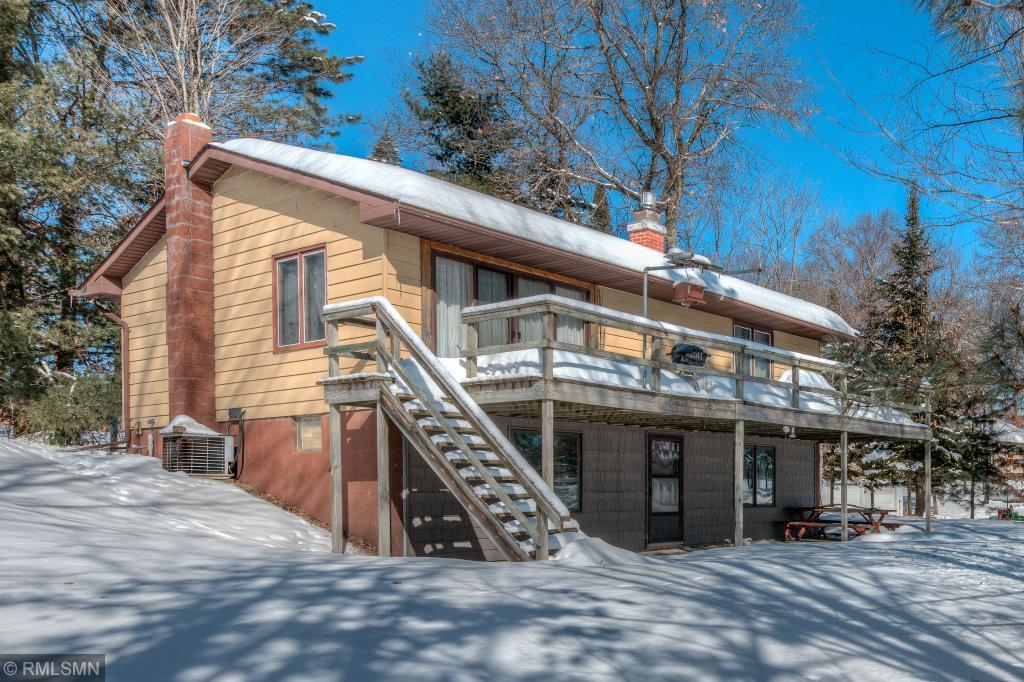 Classic year round home/cabin. Turn Key Opportunity to enjoy day 1. HUGE 4 car garage with work shop area, gradual slope to the water offering great fishing and clear waters. Hop on ATV's or snowmobile and go right from the home. 3rd bedroom needs egress, baths on both levels, newer shingles and everything you need to have North of the stress zone. 13 month HWA home warranty comes with the home. Home is dated but ready to go and finish to your liking as you wish and make those memories!!  Add'l 2 lots could be had across the road. Hurry!! Be in for the season...