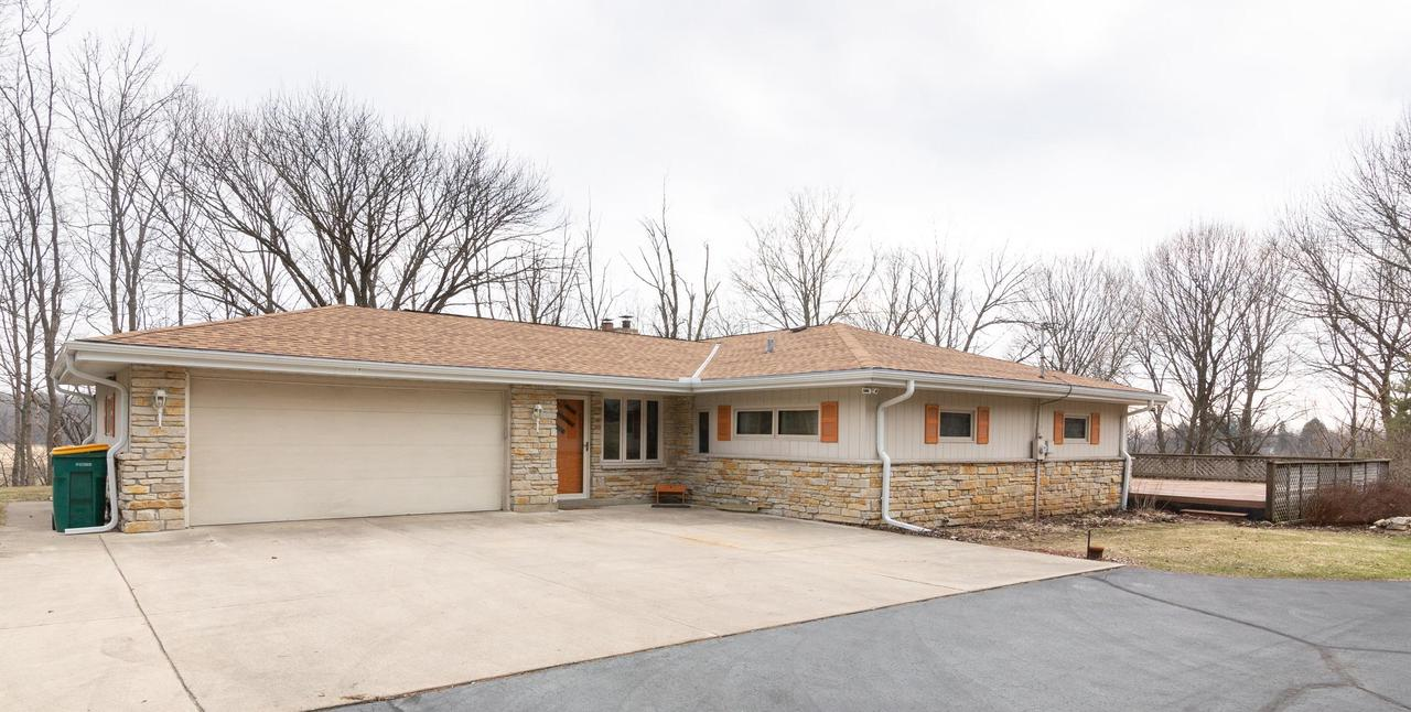 Sprawling 3BD/2.5BA ranch has 4+Car garage. Main level has 2.5 attached garage. Enter into spacious entry w/Main Level laundry/mudroom. Walk into huge kitchen, w/quartz counter tops, island and HWF open to dinette w/BIC and bonus sitting/sunroom off the kitchen. Over sized living room has NFP and lots of windows that overlook the park like 2 lot with lots of trees and perennials. 3 Generous size bedrooms all with HWF!  Lower level offers huge bonus space w/attached 1.5 car garage that opens another garage door that is a heated garage, separate drive to lower garage spaces ideal for hobbyist or small business. Basement level is heated with in-floor hydronic heat,  & has a full bathroom.  All on a 2 acre lot with pool and hot tub in good working order! A great opportunity! View Virtual Tour!
