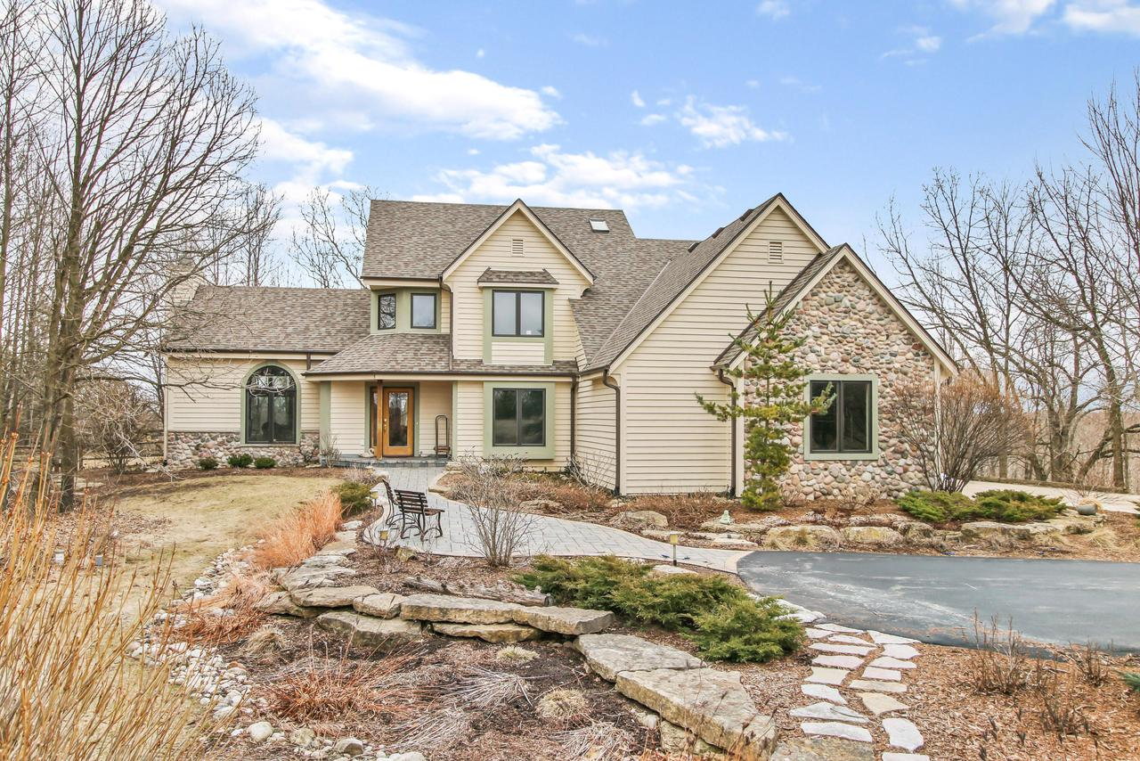 This beautiful home is one of the few home that looks a fabulous in a blooming summer as it does under a white snowy winter. Originally built for a local naturalist and her husband in 2010, the home is sighted on a small hill overlooking the 8-acre property. The home is reached via a 1/4-mile-long private drive and is not visible from the main road. The lovely home is situated on a hilltop and overlooks the surrounding countryside. The estate property is a healthy mix of Wisconsin natural habitats including native prairie, hardwood and rush wetlands, and dry hard wood forest. Please note due to the ''shelter in place'' protocols, there will be limited opportunities to see the home, please email us directly at info@teammartinrealty.com to set up a virtual visit and tour.