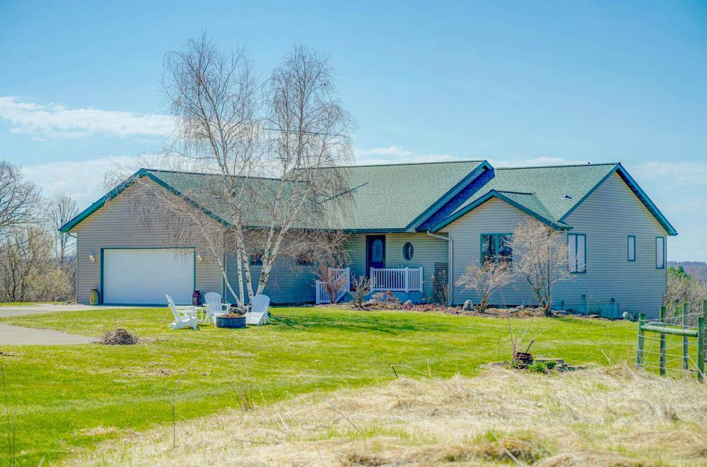 Beautiful 4BR 3BA custom home overlooking 21 acres of rolling countryside, w/ easy commuting distance to St. Paul! This home features large custom windows, hardwood floors, open floor plan, vaulted ceilings, kitchen with a large island & bar seating, & a gas FP. French doors open to a bright sunroom w/deck access for amazing views in every direction! The large master features en suite bath w/ jetted tub, separate shower, & a large walk-in closet. The LL features a family room w/ walk out to patio, in-floor heat, exercise room, full BA, & a huge mechanical room w/ plenty of shelving & storage space. The home has an oversized insul 2 car garage & 2 handsome outbuildings. The first building is 40x60 w/a concrete floor & heated shop.The second building is 36x70 w/ spray foam insulation, 5 box stalls, huge tack room, & tons of storage! 2 acre of attractive horse safe fencing, 6 acre tillable & currently rented providing add'l income & 5 wooded acres w/ wildlife all ready for your enjoyment!
