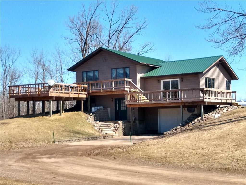 Scenic & beautiful setting on the upper portions of the Apple River. Enjoy all the beauty from over 2200 sq ft of decking facing river side. This modest 3BD, 2BA multilevel home sits on just over 8 acres which could make a great area to pasture horses or beef cattle, or a potential baseball diamond for the kids. This home offers a large front entry & kitchen/dining area plus a tuck-under garage for the toys. There is plenty of additional space for another garage or shed to be built.