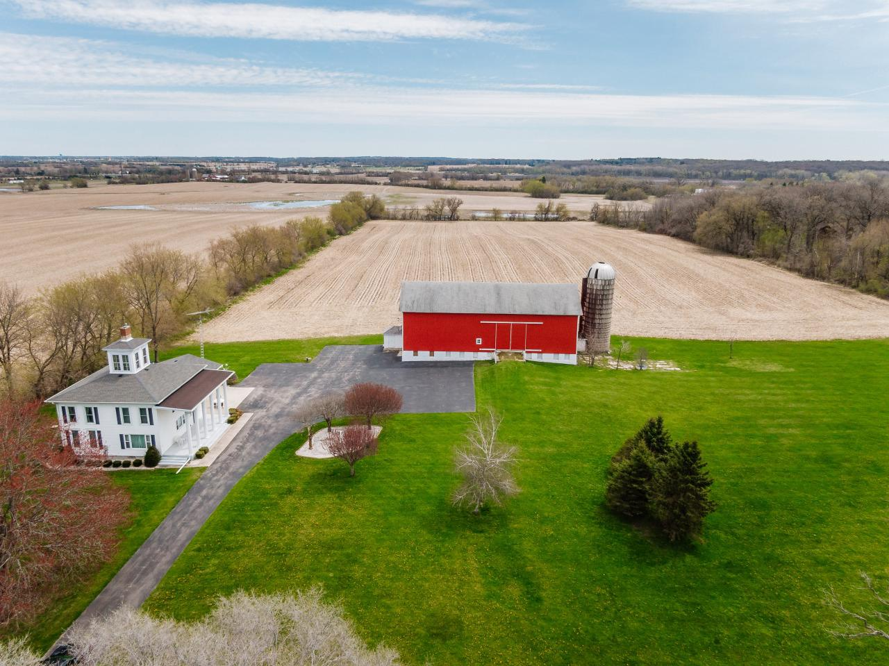 15 ACRE CLASSIC HOBBY FARM PROPERTY.  Stately 2-story, currently 2 family property with separate living on each level and private entrances. Easily combined, this is 4-bedroom 2.5 bath farm home with tall white pillars in front of home and cupola extending skyward. Gas fireplace in large living room, plenty of space in the kitchen with Master and second bedroom on main floor.   Large rec room, bedrooms 3 & 4, second kitchen and full bath on upper level.  LARGE BARN; great lawn with mature trees, level asphalt drive and large parking area and NEW WELL.  This is a GREAT OPPORTUNITY you have to see for yourself!