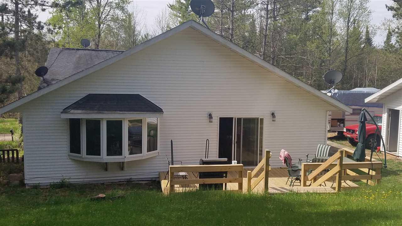 This property is on a dead end road approximately 10 miles from Rosholt. There was a 20x36  great room addition added on in 2007, cathedral ceilings with an open space. The seller states the interior needs painting and all floor coverings need to be replaced, some trim work needs to be done. Kitchen has plenty of cabinetry with an island. The living room is spacious and has a lot of natural lighting, wall shelving accents collectables. The master bedroom has a master bath with larger shower stall and main,bath has the tub. Walk down to the lower level and there is a paneled office area and a family room with walk out access. The exterior features new deck ,a smaller horse stable, a 10x12 building with a hot tub (interior needs finishing) Newer detached 24x28 vinyl garage with cement floor. Old 2 car detached garage. 500 gallon LP tank is owned. This property has River Rd dividing the parcel so the Little Wolfe River is opposite of the home and buildings. Seller states about 175' of water frontage.  There is state owned property neighboring this property for public fishing and hunting!