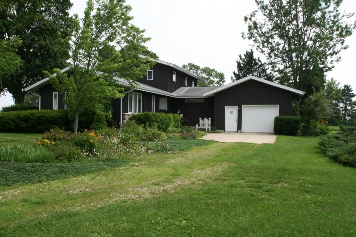 You will know your are home! Perfect space for living, entertaining & relaxing. Beautiful Walnut woodwork accents much of this home. Eat in kitchen is complete with pantry, space for 2 refrigerators or freezer + gas stove. Opens to large dining area that is complete w/ patio door to porch which is a perfect space to gather/relax and watch the fireflies a night. Great Room w/ floor to ceiling stone NFP hand split by owner. Abundance of windows, 5 nice size bedrooms, 1 bed on main, 1.5 baths, FF laundry. Fiber optics available! Gardener's dream w/ years of collecting and planting flowers, flowering trees & bushes + some edibles. Barn & Milk House supported the dairy farm before they became a carpenter's shop. Outbuildings offer storage for all your needs. Minutes from Lake Geneva & Airport.