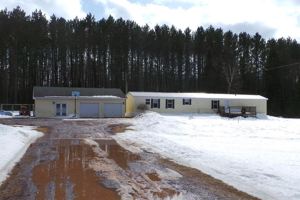 """This attractive, well maintained 14x70 3 bed, 2 bath mobile home has a 2 car garage w/ an additional heated, insulated """"whatever you want it to be"""" room that has a kitchen, full bath, & office area. The outdoor wood burner heats the house & garage very efficiently. There is also a LP forced air furnace. This property sits on 50 acres of country land. There is 15 acres of field & the rest is wooded."""
