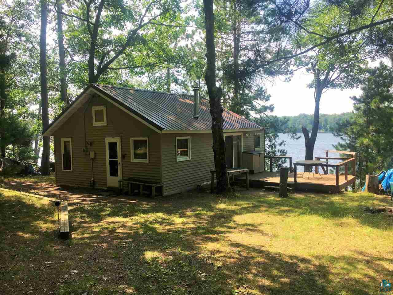 Rustic 2 bedroom, 1 bath cabin with deck, dock and one car garage on Deep Lake. Beautifully wooded 100' lot features sandy swimming frontage with afternoon sun. Small wood stove is perfect for taking the chill out on cool evenings.