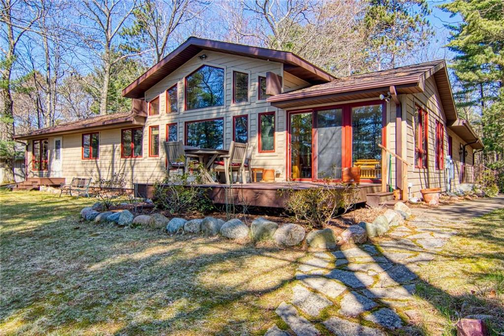 Beautiful Easterly views of Big Sissabagama Lake from this chalet ranch style home. This well maintained home sits on a 1.6 acre parcel w/100 ft. of hard sand bottom frtg. There is a two-car-att. garage as well as a one car det. garage/workshop for extra storage. Home offers everything on one level with all BRs facing the lake. As you enter the home you walk into the large living room w/tongue & groove cathedral ceilings & a wall of windows to take in the lake views. A large wood-burning stone faced fireplace accents the living room. Kitchen is large & offers plenty of room for prepping meals. There is also an informal dining area in the kitchen as well as a formal dining area just off the living room, or enjoy your meal outside on the lakeside deck.  On main level is a large master BR with it's own private door to lake side & 2 BRs (one currently an office) that share a full BA. Half BA/laundry room that completes the upper level. There is also a small wood burning stove in workshop.