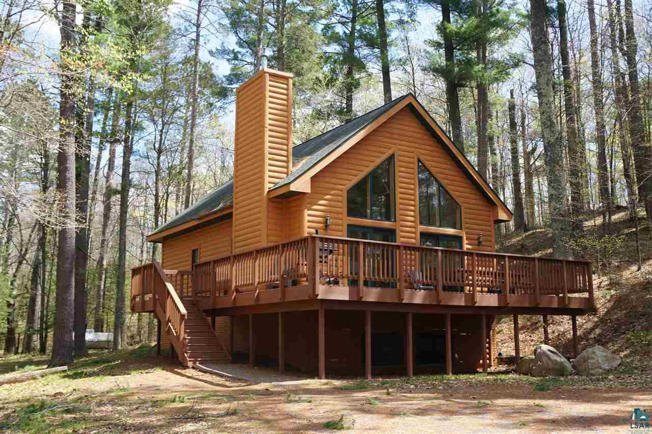 Enjoy this 4 bedroom Chalet Style year round home in Deer Trail Lodge Condo Assoc. or use it as income property.  This unit is set back in a private wooded area and yet as part of the association, has use of the Lake, beach and a designated  dock space for a boat or pontoon.  Great Rental History!