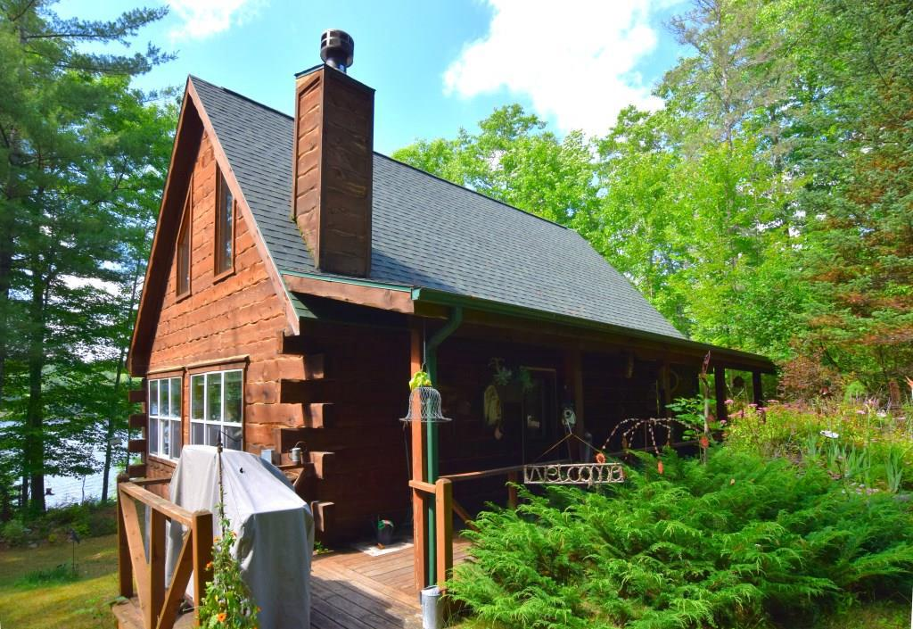 Privately-situated log chalet on Hunter Lake!  Vaulted pine ceilings over sun-filled great room w/stone wood-burning fireplace & wood floors.  1 bdrm & bath w/shower on main floor.  Screened porch w/beautiful lake views!  2-room loft - use as 2 sleep areas or use smaller rm as walk-in closet.  22 steps to lake, plus shoreline boat winch (needs repair). Sand bottom shore w/few weeds (clear with use) Perennial-landscaped yard & firepit.  Unfinished walkout bsmt w/laundry. ATV/snowmobile & more!