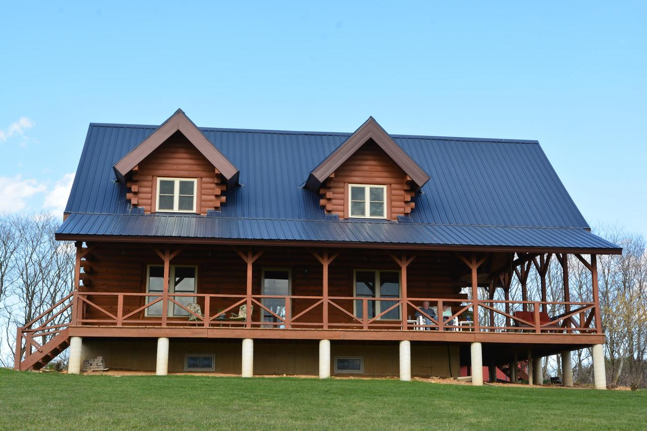 This idyllic log home embodies all the tranquility, warmth, and stillness that comes to mind when one imagines log home living. It's incredibly spacious yet incorporates the cozy warmth of traditional log cabin living; it's rustic and charming yet offers many modern amenities and conveniences. Inside you'll find comfortable living combined with an extremely functional open floor plan that flows seamlessly from one room to another and its expansive deck embraces the outdoors while offering superb views of the tranquil surrounding countryside. It also features an electrified 24'x32' detached metal garage with covered lean-to and entrance and 10'x16' Amish-built storage shed.