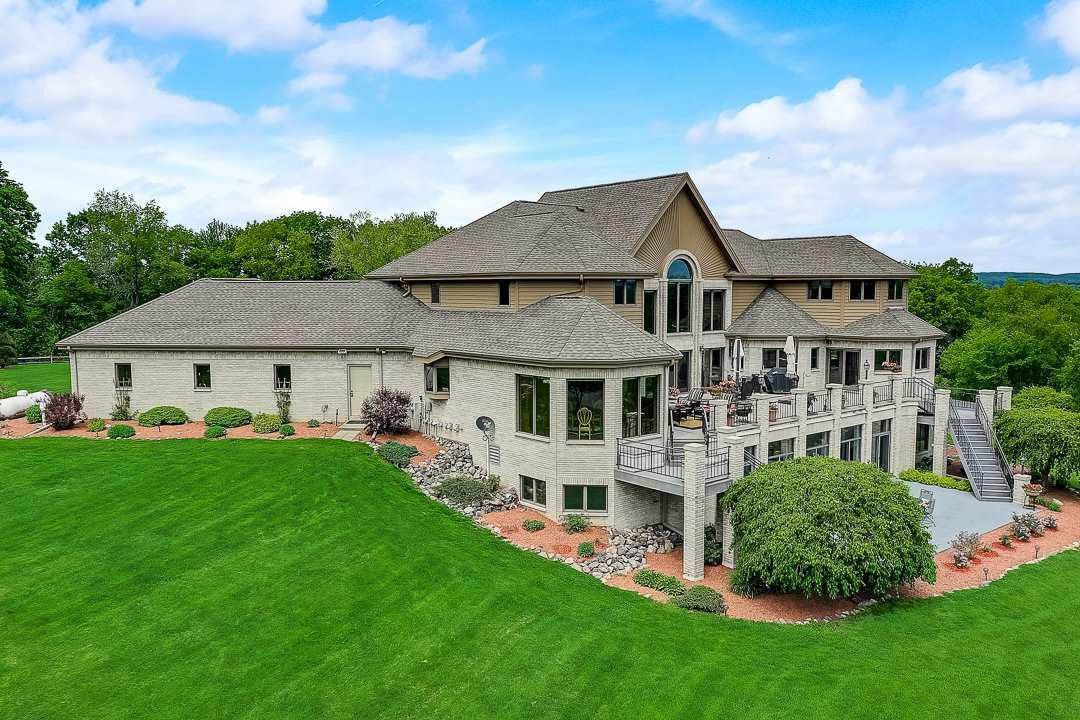 Autumn Manor estate sits on 60 pastoral acres in Sauk County.Rolling hills, spacious views, pristine pastures, 1.5 acre fishing pond, terraced by the Baraboo River sets the stage for this spectacular home.The perfect blend of country charm and elegance. This impressive home boasts large sun filled rooms with views of the beautiful grounds, vaulted ceilings, fabulous island kitchen with dreamy main floor master suite. Large deck and patio with attached indoor pool is the perfect place for entertaining and relaxing with family & friends.The property spotted with bronze Remington statues accentuate the long tree lined drive to paradise. Let your horses or animals enjoy the split rail fenced pastures, or let them run in the 90 x 110 stable with indoor riding arena. Time to make new memories.