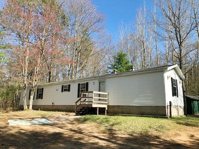Tucked away in the woods! A nice country setting for this 2 bedroom, 2 bath mobile home located on a 0.75 wooded parcel. Offers an open concept KT/DR/LR design with patio doors that lead to a large deck that overlooks the backyard. Master bath with separate shower/tub. Utility/laundry room. Full block foundation on slab w/crawlspace. Storage shed. Has snowmobile trail access and it's just a short ride to town for conveniences. A great place to call home!