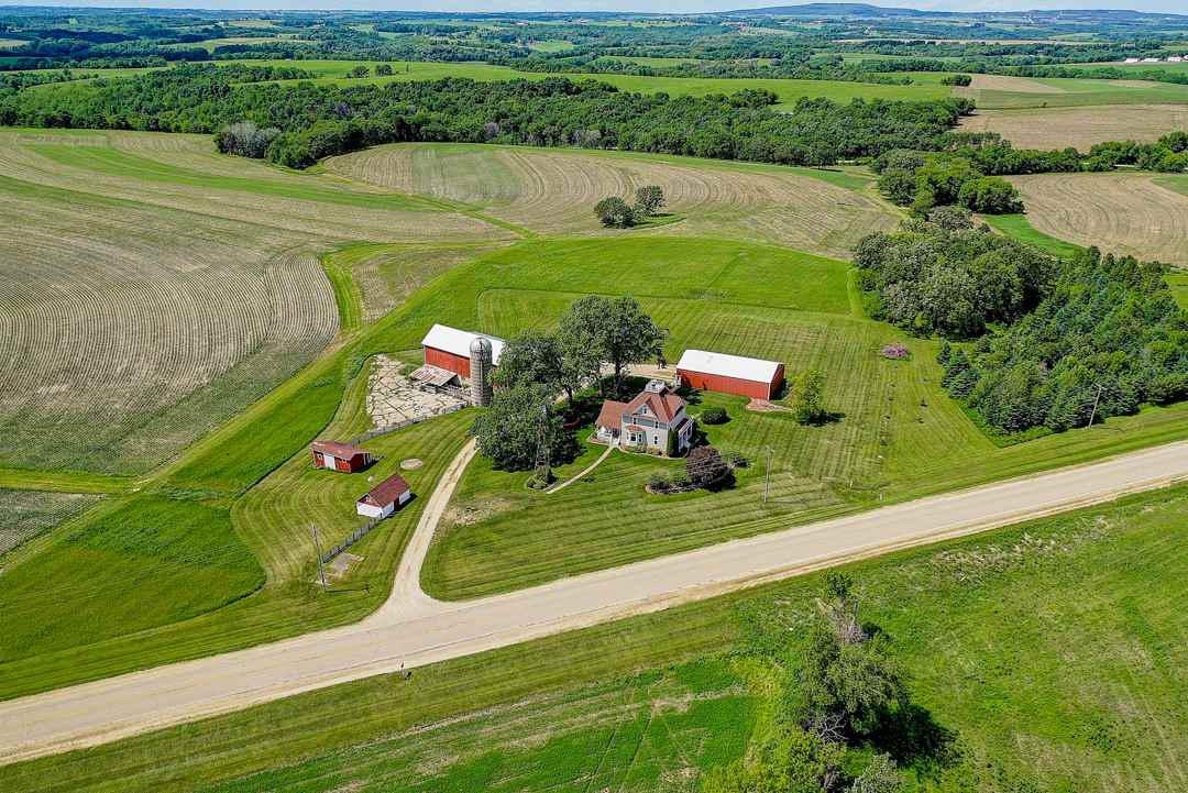 Looking for privacy, room to breath & beautiful views in Mt Horeb SD? Welcome home! 4 bdrm colonial farmhouse on 6 acres.  Gorgeous trim work & doors accent the home w/family friendly layout, good natural light, wood floors throughout, reclaimed barnboard on walls. A free standing stove warms up the LR, updated elect & new fixtures, new a/c. New SS appliances in kitchen. Generously sized bedrms & master w/walkin. Walk up attic for storage or to finish off & LLFR. Three car garage w/tons of addit'l storage in same bldg behind--all heated & insulated. Bldg is 40x40. Older barn, silo, chicken coop, dog barn w/heated water. Swim in heated, 2yr new above ground pool! Sm patio & firepit. Elect fence-all parts includ. Main flr bdrm could be an office. About 12 min to schools & downtown Mt Horeb!