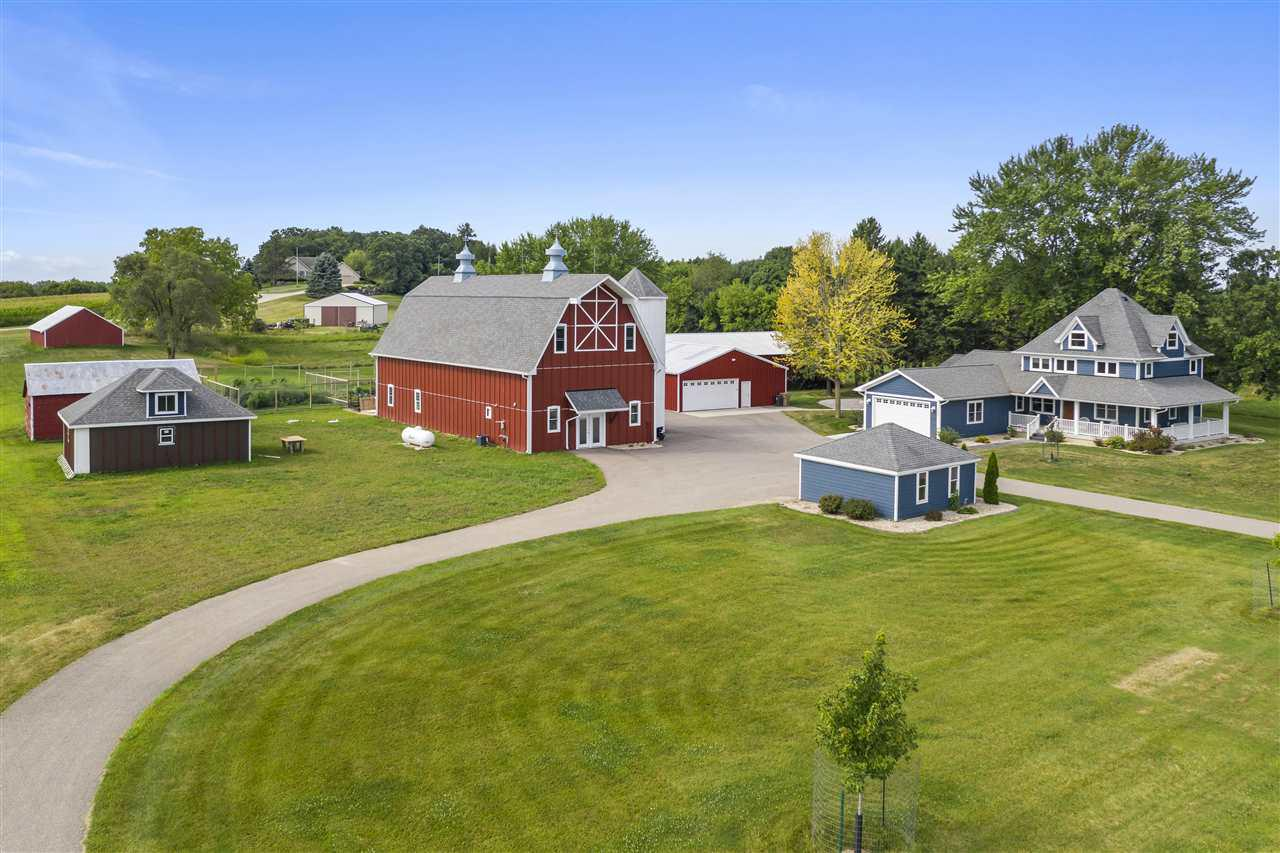 Owned by a builder, this stunning 4-bed, 2.5 bath farmhouse (complete w/ wrap-around porch!) on 5 acres on the outskirts of Madison has been completely remodeled & is a must-see property! Main flr features an ideal open concept living space and the kitchen's white cabinetry, granite countertops, SS appliances & lg island will not disappoint. Large mudroom & spacious master w/ensuite/walk-in closet also on main level. 3 sizable bedrooms, full bath upstairs & add'l, usable attic space. Look no further if you need outbuildings! All updated w/ their own electrical service...shops: 30x36-heat/cooled & 36x90, 30x71 barn (w/office, full bath & amazing workshop, potential for a gorgeous event space upstairs), 12x18 detached garage, 20x20 shed. Original chicken coop w/water/elec.
