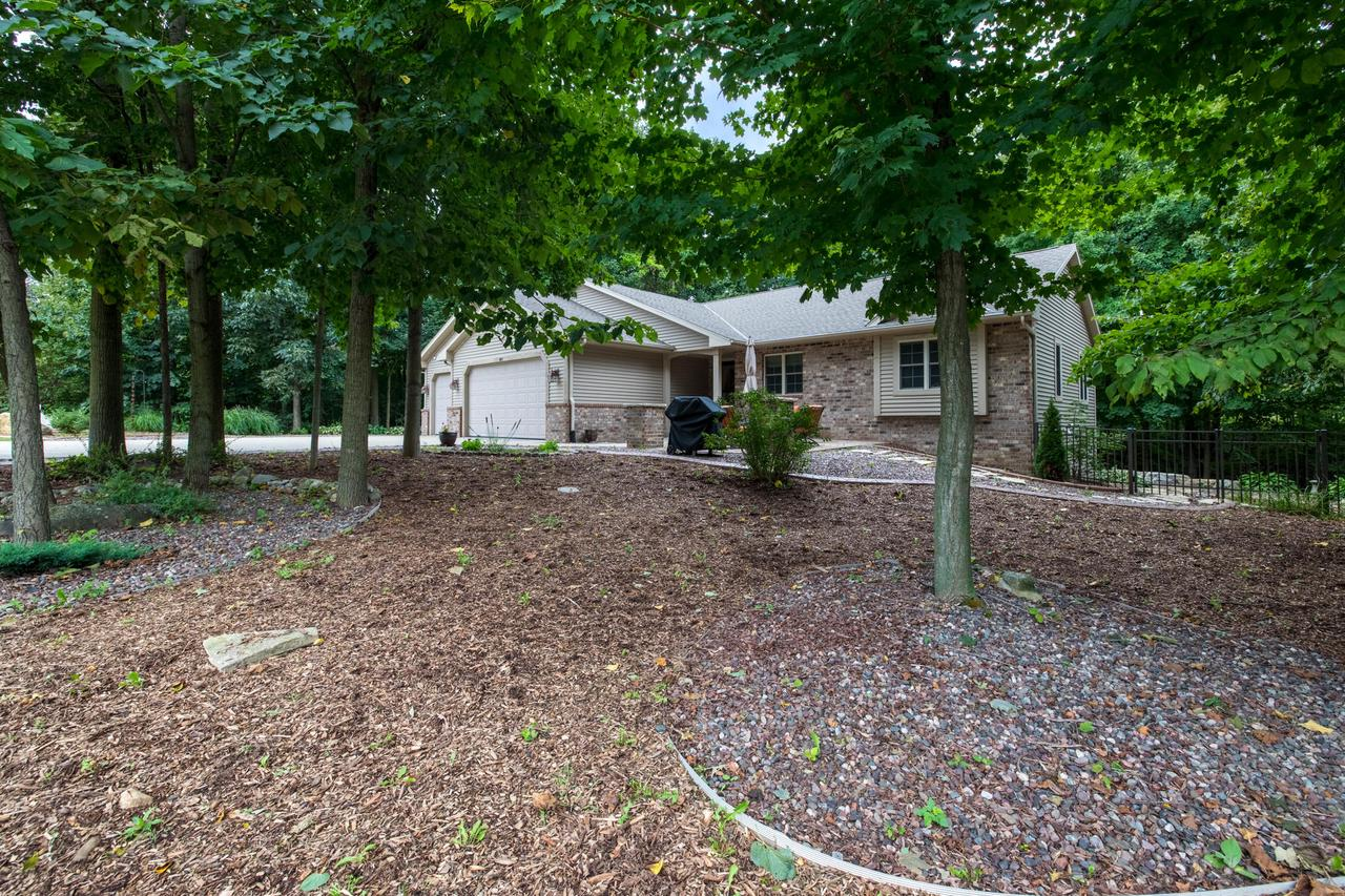 Only a job transfer makes this home available! 4 bedroom, 3 bath ranch home in a quiet neighborhood sits on 1.8 acre wooded lot! Open concept living with vaulted ceilings and cozy gas fireplace are sure to please. Kitchen features stainless steel appliances and plenty of storage, prep space and seating. 3-season room right off dining area with a view of the creek below in a tranquil, private setting. Nicely landscaped with stone front patio and fire pit area. New aluminum containment fence installed 2020. Finished basement with full size windows for added entertainment space along with 4th bedroom and 3rd full bath. Slinger Schools!