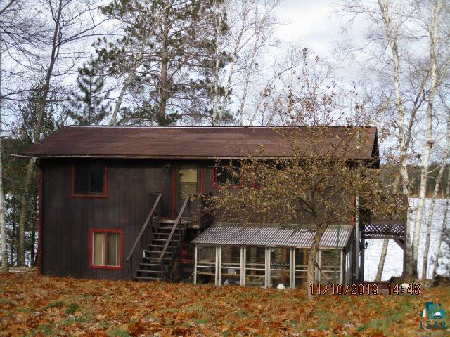 Lake Front Property!!!!!  All natural wood work inside, beamed ceilings, and two stone and tile areas ready for gas stoves.  There is a porch, deck, and lake front on Iron Lake.
