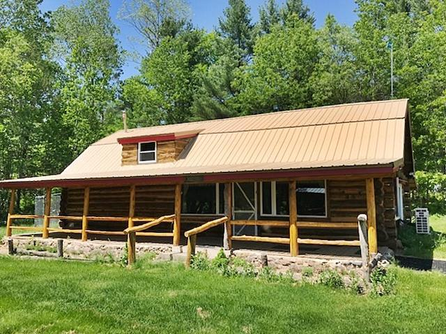 Perfect northwoods setting! Well maintained 2 BR, 2 bath authentic log home on 6+ acres. Features a picturesque view from every window. Main floor offers kitchen w/custom cabinets, 14x7 walk in pantry, gas fireplace, bedroom and bath w/laundry. Hickory flooring. Upper floor has a huge 28' x 18' 2nd bedroom and 2nd bath. New 2-zone ductless split air/heat pump. Covered front porch overlooks the beautiful manicured yard highlighted with apple trees, berry bushes and perennial flowers. Pavilion w/firepit that complements a tranquil view of the pond. New 30' x 40' heated 4 car det. garage. Large 16' x 12' shed for extra storage along with a custom built adorable log garden shed/dog kennel. Nestled at the end of a quiet dead end road for seclusion and yet close enough to small town conveniences